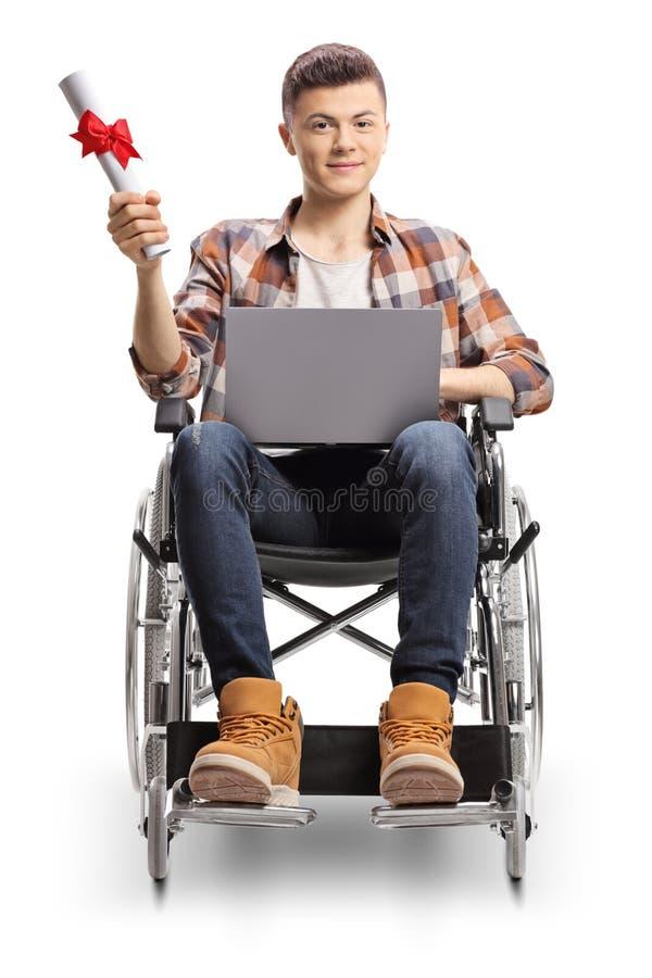 Jonge mannelijke student in een rolstoel met laptop en een graduatiecertificaat stock foto's