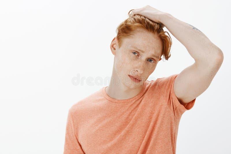 Jonge mannelijke student met rood haar en sproeten die bij spiegel en wat betreft kapsel staren, die kapsel denken te veranderen stock afbeeldingen