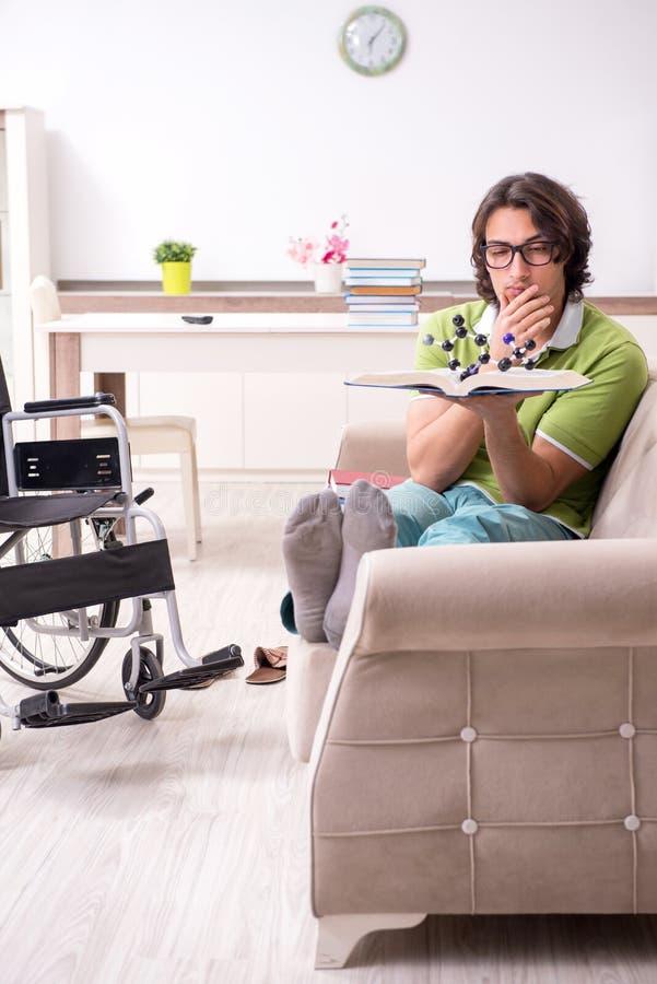 Jonge mannelijke student in rolstoel thuis stock fotografie