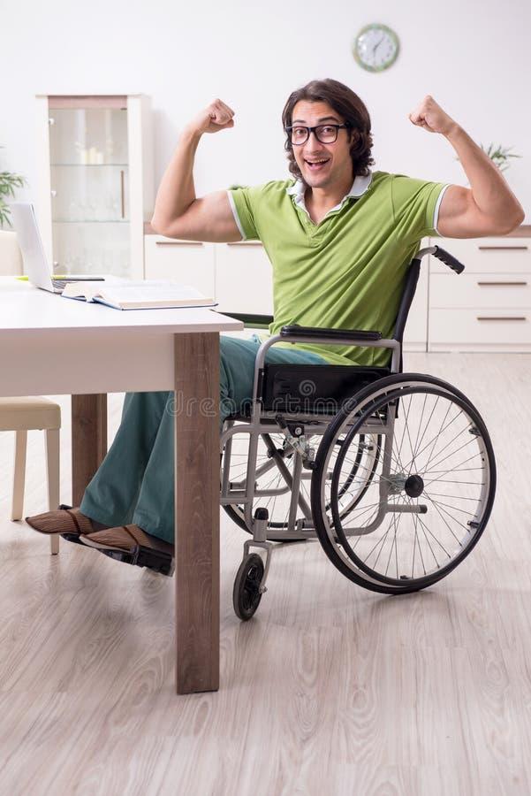 Jonge mannelijke student in rolstoel thuis stock foto