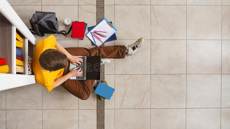 Jonge mannelijke studentenzitting bij boekenrek en het gebruiken van laptop royalty-vrije stock fotografie