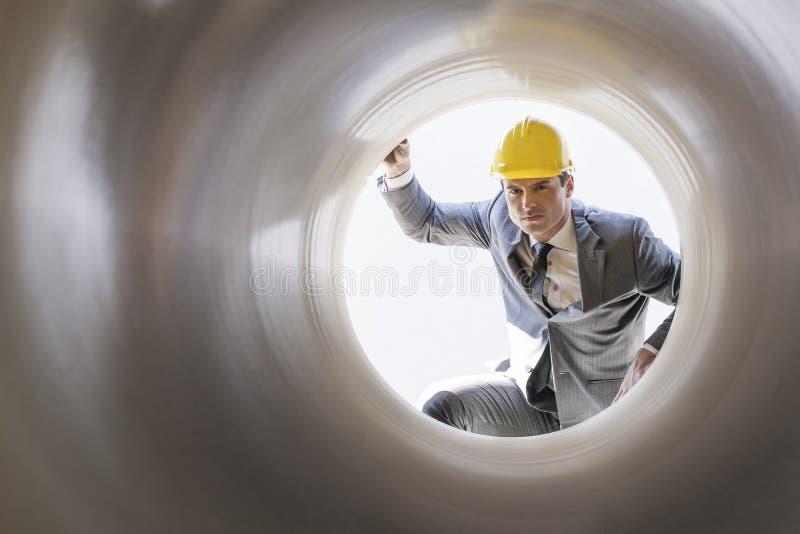 Jonge mannelijke supervisor die grote pijp onderzoeken bij bouwwerf royalty-vrije stock afbeeldingen