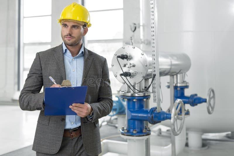 Jonge mannelijke supervisor die op klembord in de industrie schrijven stock foto's