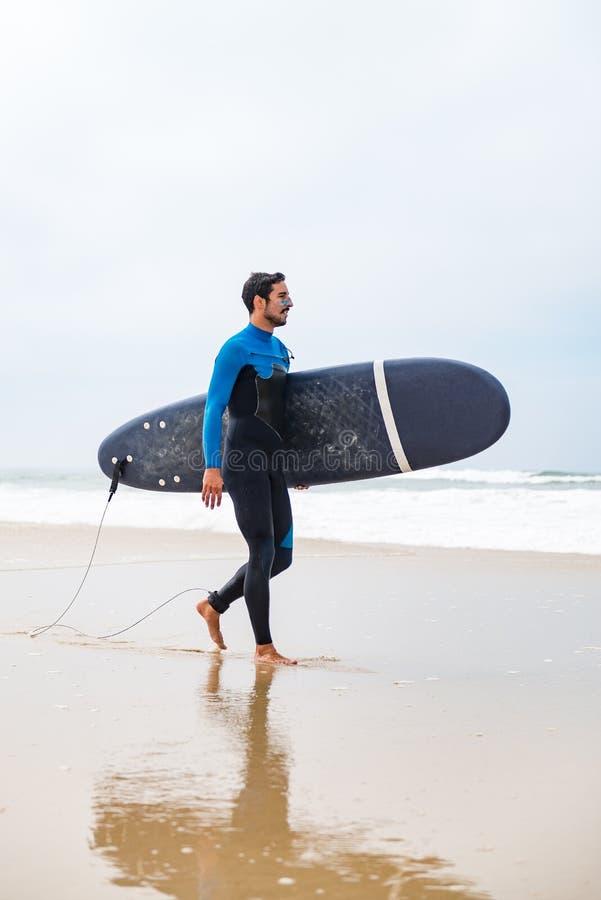 Jonge mannelijke surfer die wetsuit dragen stock fotografie