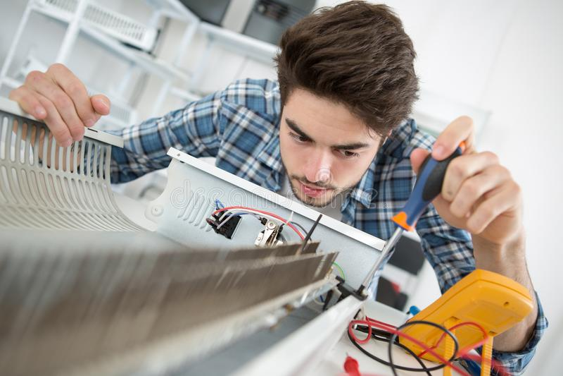 Jonge mannelijke technicus die radiator met schroevedraaier controleren royalty-vrije stock afbeeldingen