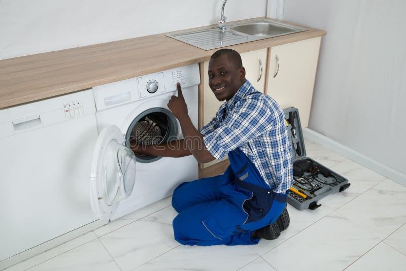 Jonge Mannelijke Technicus Fixing Washing Machine royalty-vrije stock foto's