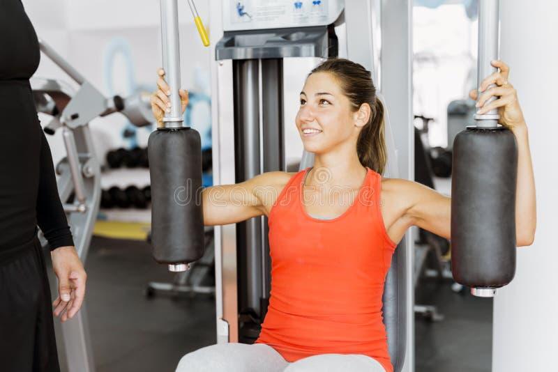 Jonge mannelijke trainer die instructies geven aan een vrouw in een gymnastiek royalty-vrije stock afbeelding