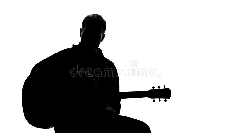 Jonge mannelijke van de musicuszitting en holding gitaar bij auditie, die lied uitvoeren royalty-vrije stock foto's