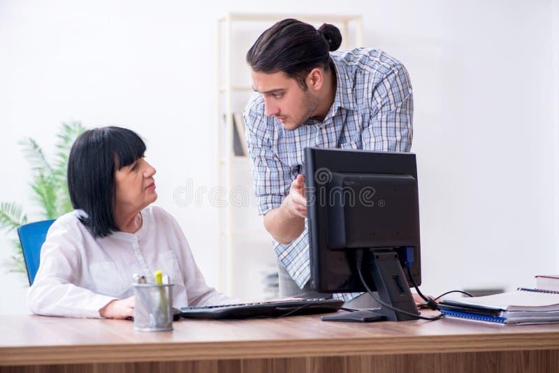 Jonge mannelijke werknemer die aan oude vrouwelijke collega hoe te ons verklaren royalty-vrije stock afbeelding