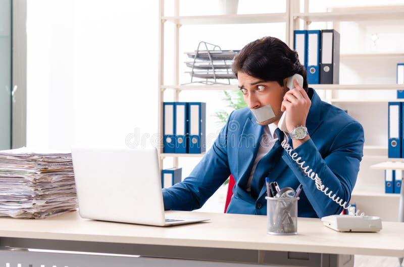 Jonge mannelijke werknemer met band op de mond stock afbeelding