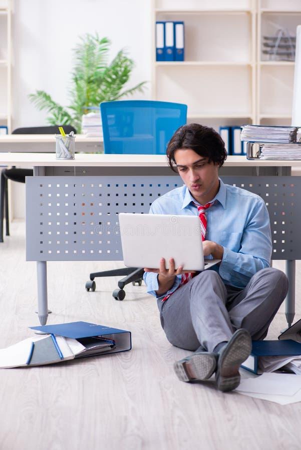 Jonge mannelijke werknemer ongelukkig met het bovenmatige werk stock foto's