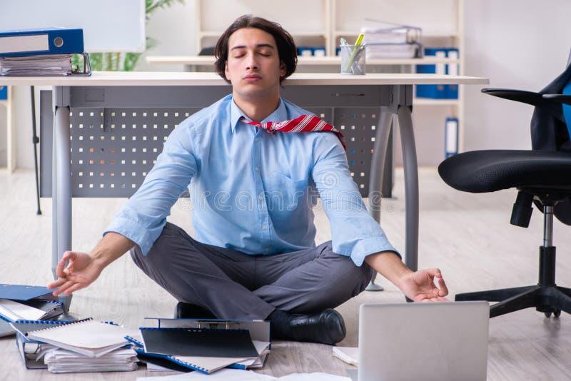 Jonge mannelijke werknemer ongelukkig met het bovenmatige werk stock afbeeldingen