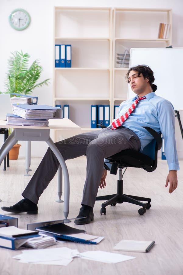 Jonge mannelijke werknemer ongelukkig met het bovenmatige werk royalty-vrije stock afbeelding