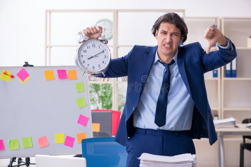 Jonge mannelijke werknemer ongelukkig met het bovenmatige werk royalty-vrije stock foto's