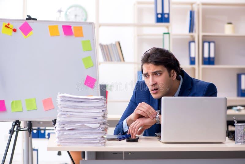 Jonge mannelijke werknemer ongelukkig met het bovenmatige werk stock foto