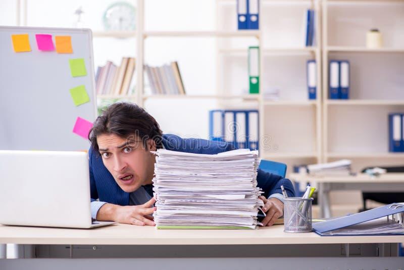 Jonge mannelijke werknemer ongelukkig met het bovenmatige werk royalty-vrije stock fotografie