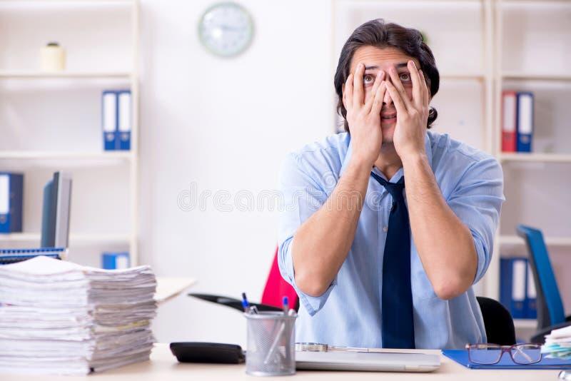 Jonge mannelijke zakenmanwerknemer ongelukkig met het bovenmatige werk stock foto