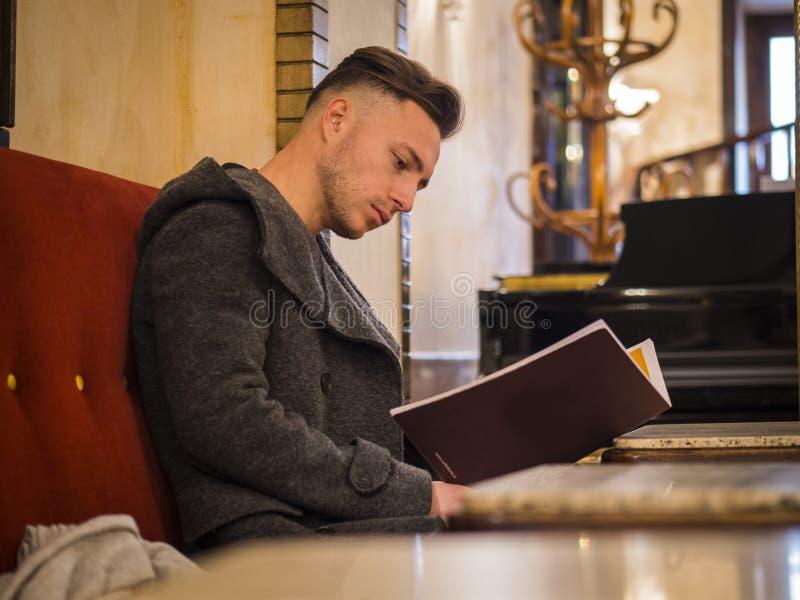 Jonge in mannelijke zitting door lijst en lezingsmenu in koffie royalty-vrije stock afbeeldingen