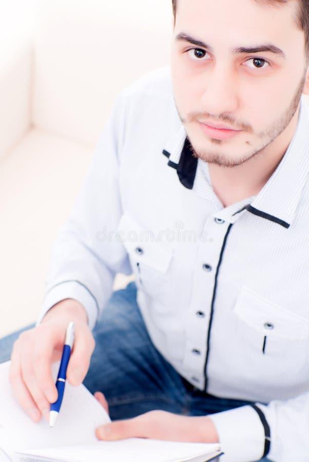Jonge mannelijke zitting op laag stock foto