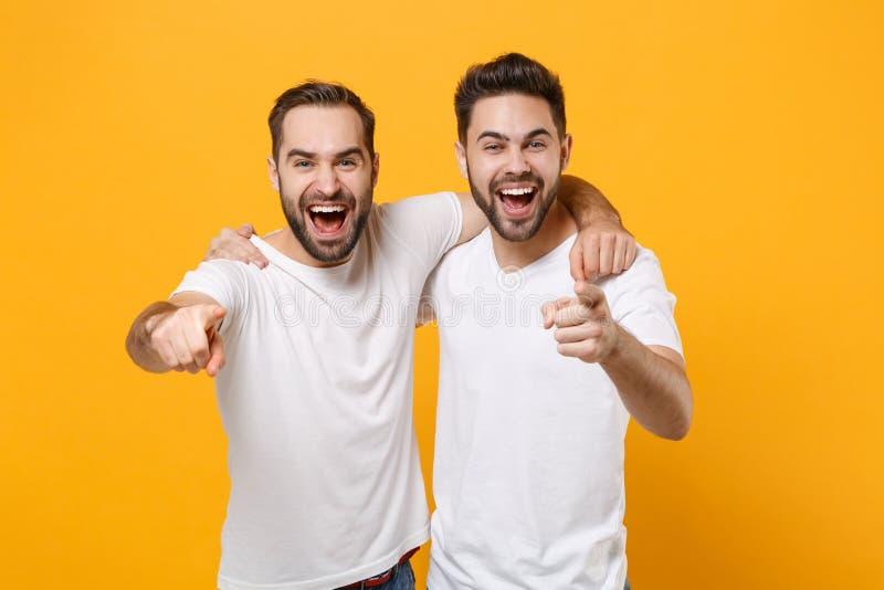 Jonge mannen lachen vrienden in blanke lege t-shirts die zich afschermen op gele oranje achtergrondstudio stock foto's