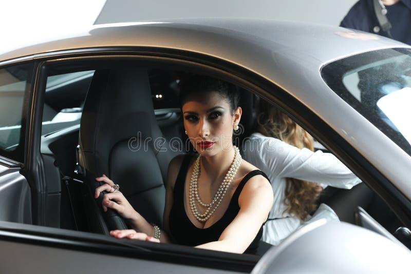 Jonge Mannequin With Parelhalsband het Stellen in een Porsche-Sportwagen royalty-vrije stock foto