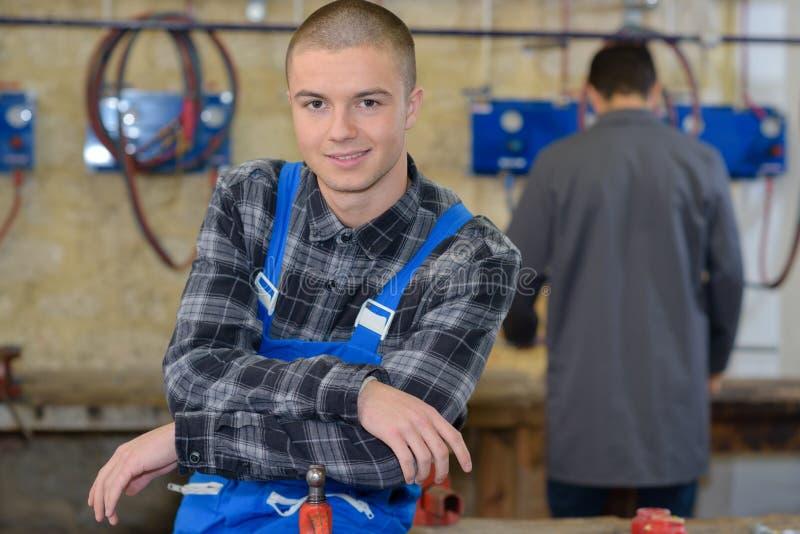 Jonge mechanische leerlingen in workshop stock afbeelding