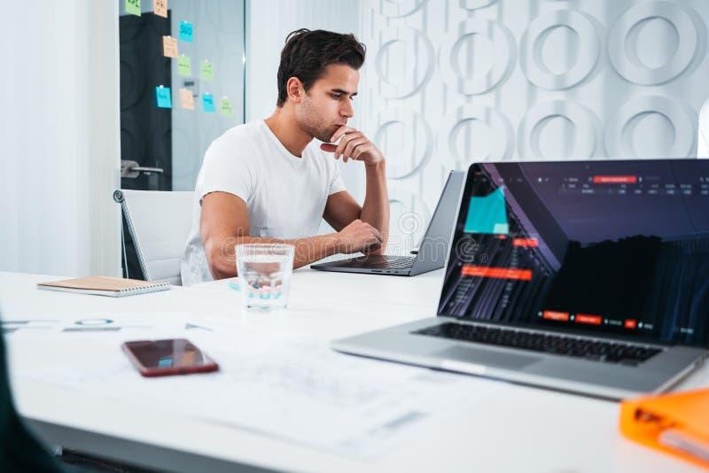 Jonge medewerkersmensen die op het kantoor werken van de het werkplaats terwijl het zitten bij lijst en het analyseren van tenden royalty-vrije stock foto's