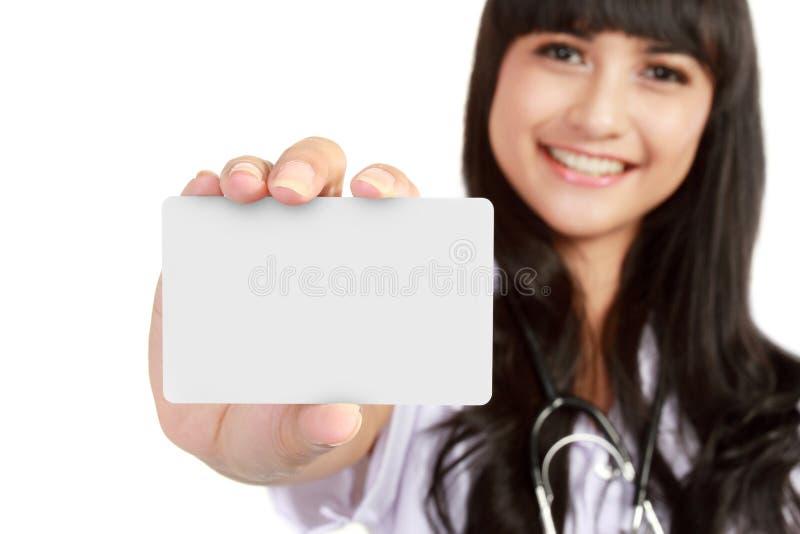 Jonge medische artsenvrouw die adreskaartje toont stock afbeelding