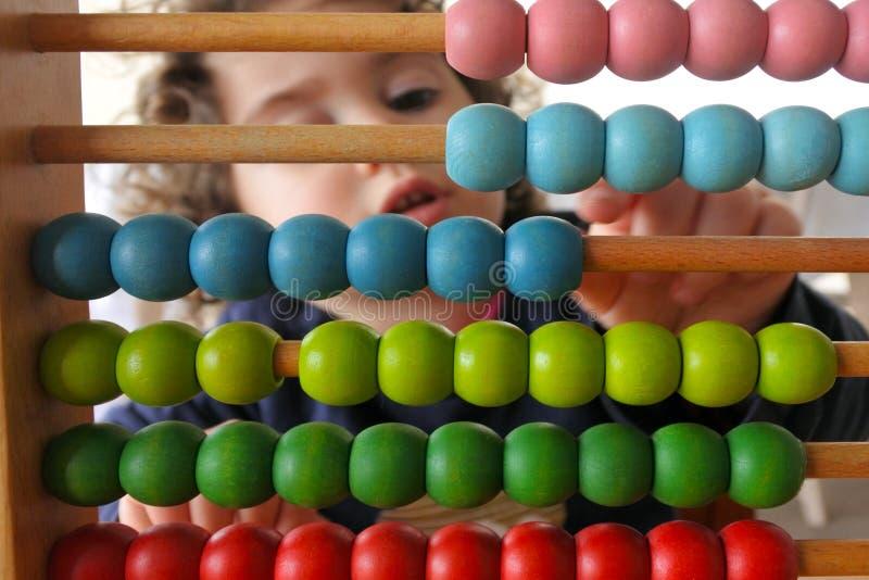 Jonge meid die op Abacus rekent stock foto