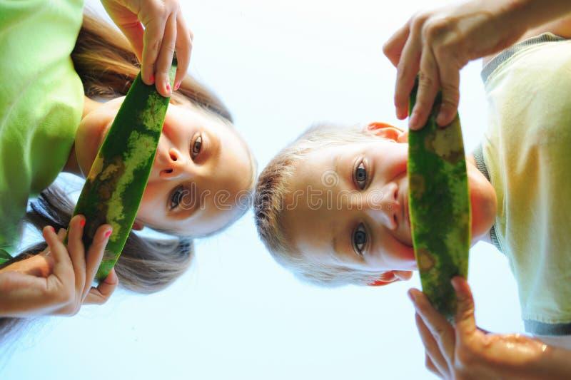 Jonge meisje en jongen die watermeloen eten stock fotografie