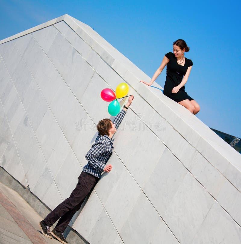 Jonge meisje en jongen tegen blauwe hemel royalty-vrije stock afbeeldingen