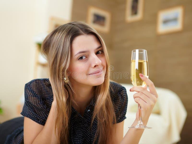 Jonge meisje het drinken champagne thuis royalty-vrije stock afbeeldingen