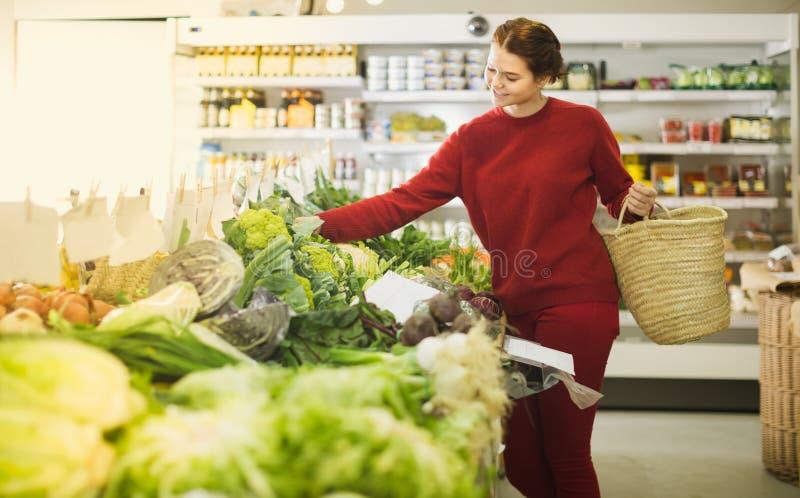 Jonge meisje het kopen bloemkool bij markt stock afbeelding