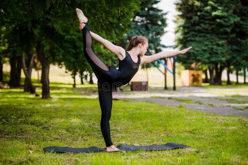 Jonge meisje het praktizeren yoga in aard in het hout op een achtergrond van groen bomen en gras Zij brengt op één been in evenwi stock foto