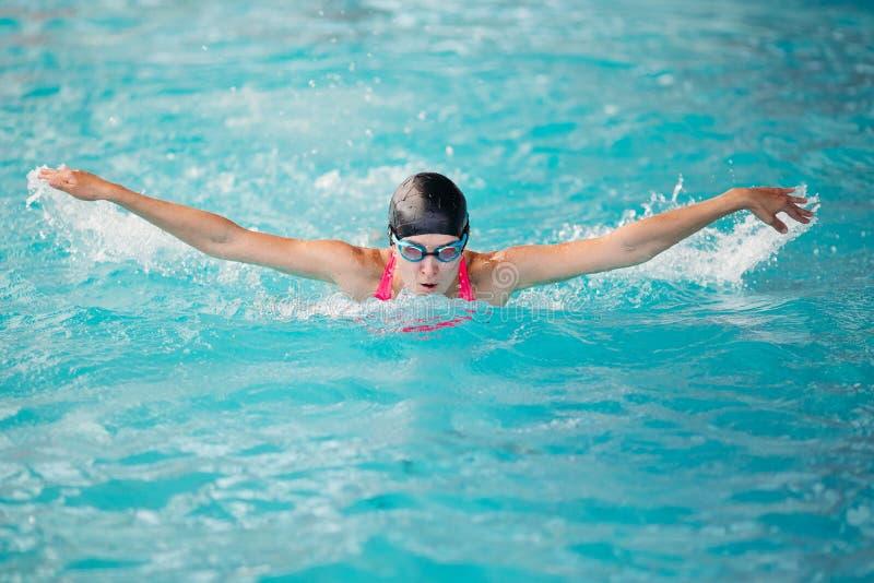 Jonge meisje het zwemmen vlinderslagstijl in blauwe waterpoo stock afbeelding
