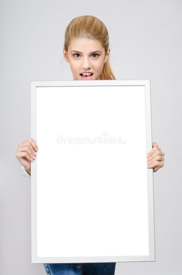 Jonge meisje verbaasde holding vooraan een witte lege raad. stock afbeeldingen
