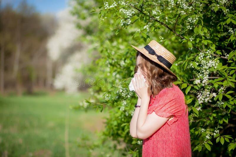 Jonge meisjes blazende neus en het niezen in weefsel voor bloeiende boom Seizoengebonden allergenen die mensen be?nvloeden E stock foto