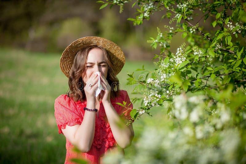 Jonge meisjes blazende neus en het niezen in weefsel voor bloeiende boom Seizoengebonden allergenen die mensen be?nvloeden E royalty-vrije stock fotografie