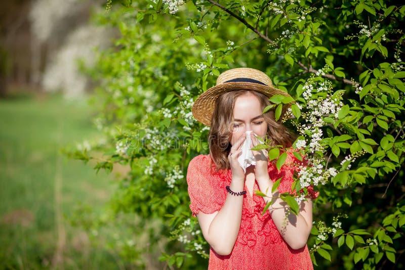 Jonge meisjes blazende neus en het niezen in weefsel voor bloeiende boom Seizoengebonden allergenen die mensen be?nvloeden E royalty-vrije stock foto's
