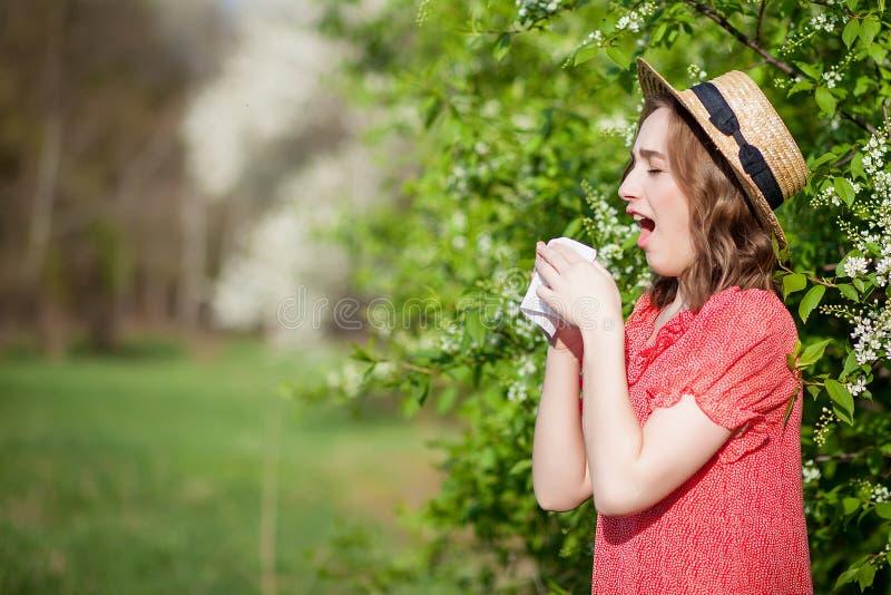 Jonge meisjes blazende neus en het niezen in weefsel voor bloeiende boom Seizoengebonden allergenen die mensen be?nvloeden E royalty-vrije stock foto