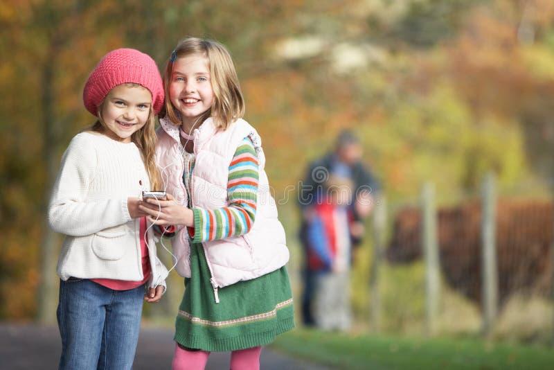 Jonge Meisjes die aan MP3 Speler in openlucht luisteren royalty-vrije stock fotografie
