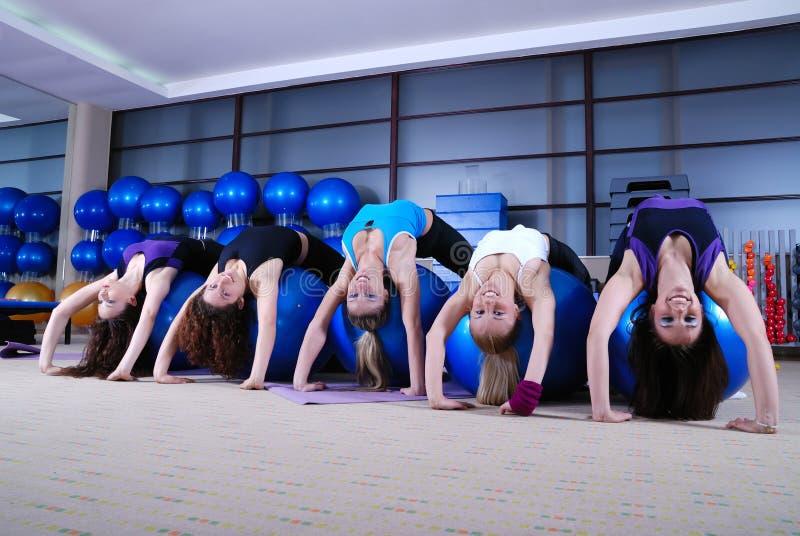 Jonge meisjes die in een gymnastiek uitwerken stock foto's