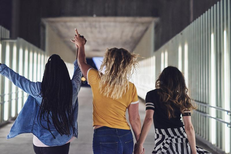 Jonge meisjes die handen houden terwijl het lopen samen bij nacht stock foto