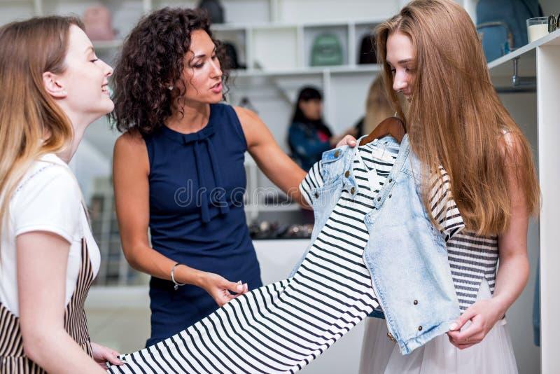 Jonge meisjes die nieuwe kleren kiezen die, evaluatie, die een kleding in kledingswinkel bespreken bijeen blijven stock afbeeldingen