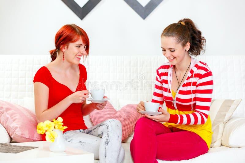 Jonge meisjes die op bank en het drinken thee zitten stock foto