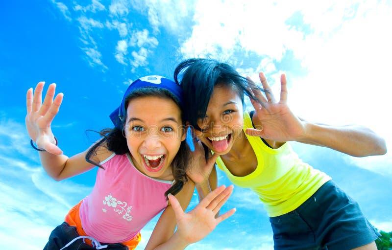 Jonge meisjes die pret hebben die grappige gezichten maakt stock afbeeldingen