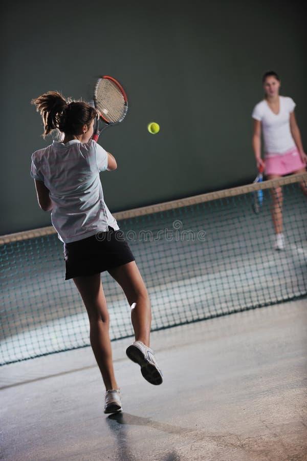 Jonge meisjes die tennisspel spelen binnen royalty-vrije stock afbeeldingen