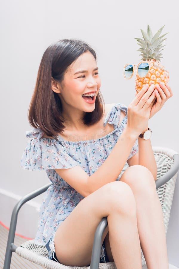 Jonge meisjes gelukkige glimlach en vrolijk in blauwe kleding en greepananas ter beschikking, Slijtagezonnebril met een weerspieg royalty-vrije stock afbeeldingen
