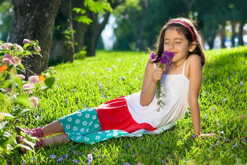 Jonge Meisjes Ruikende Bloemen in Haar Handen royalty-vrije stock foto
