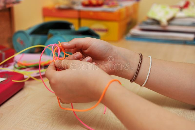 Jonge meisjes` s handen die een plastic armbandclose-up weven stock foto's
